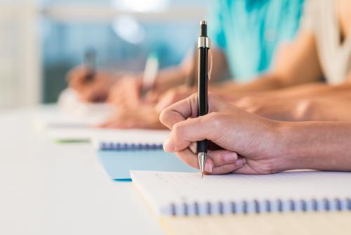 Mano con penna che scrive su un blocco note